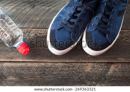 Sport shoes and water on wooden background . Sport equipment top view