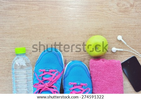 Sport shoes and water with set for sports activities on tiled floor.