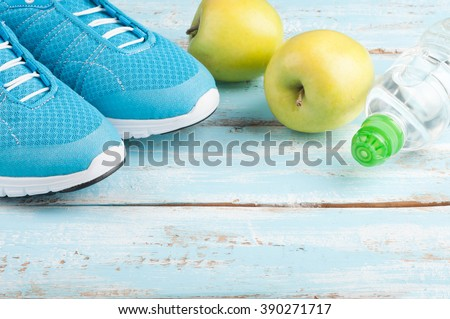 Sport shoes, apples, bottle of water on blue wooden background. Concept healthy lifestyle, healthy food, sport and diet. Sport equipment. Selective focus