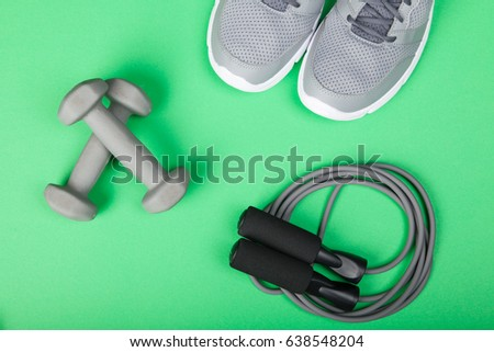 Sport shoes, dumbbells and skipping rope on green background. Top view. Fitness, sport and healthy lifestyle concept.