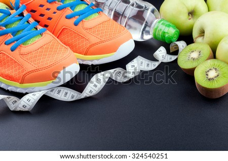Sport shoes, fruits,  bottle of water and measuring tape on dark background. Sport equipment. Concept healthy life, sports and diet. Selective focus