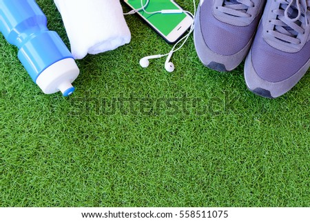 Sport shoes, mobile phone, blue water bottle and white towel on green grass background.Sports equipment on green grass background. #558511075