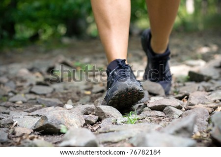 Sport shoes on trail walking running in mountains. Jogging or training outside in summer nature, motivational health and fitness concept.