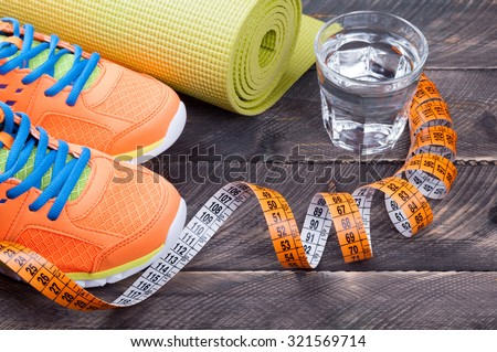 Sport shoes, yoga mat,  glass of water and centimeter on wooden background. Sport equipment. Concept healthy life. Selective focus