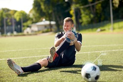sport, sports injury and people - injured soccer player with ball on football field
