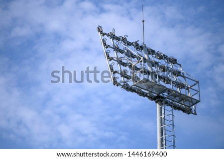 Sport stadium spotlight with blue sky background. Football and soccer light lamp #1446169400