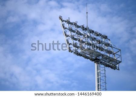 Sport stadium spotlight with blue sky background. Football and soccer light lamp