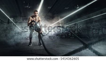 Sport. Strong man exercising with battle ropes at the gym with. Athlete doing battle rope workout at gym. Dramatic sports background.