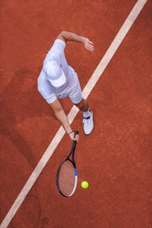 Sport. Top view of male tennis player hitting ball with racket.