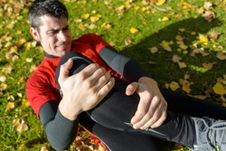 Sport training tibia fracture injury. Male athlete grabbing painful leg.