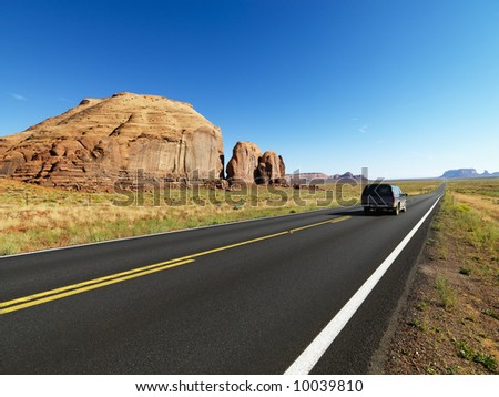 Sport utility vehicle on open highway in scenic desert landscape with butte land formation. - stock photo