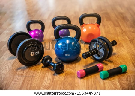 Sport weight, Ab. roller wheel , dumbbells and kettlebells on wooden floor in gym