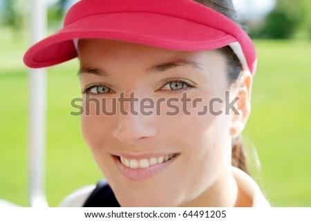 sport woman closeup portrait face smiling sun visor cap tennis golf
