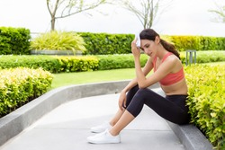 Sport woman gets tired and get dizzy when she jogging or exercise outdoor with strong sunlight in hot weather. She will be fainting after exercise. Beautiful girl get heatstroke. She taking a rest