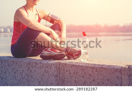 Sport woman having a rest during training outside in city quay in the morning