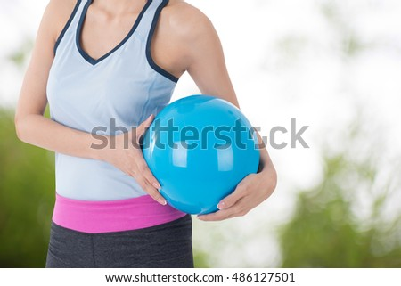 sport woman holding beach ball with blur tree picture in background #486127501
