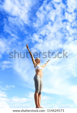 Sport woman on top of the mountain reaches for the sun. Young fit woman in sports clothing, with spread arms, looking at blue sky.