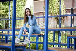 Sport woman sitting and smiling on tribunes outside. Young attractive girl model in stylish sport clothing.