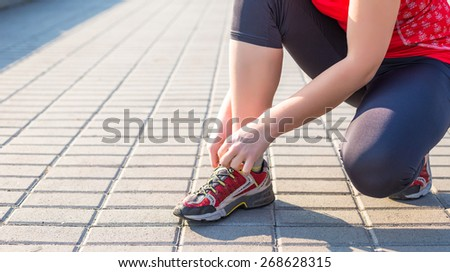 Sport woman tying running shoes during training in park in the morning