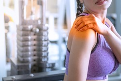 Sport women fitness have injury muscle joint between shoulder and arm pain after workout in gym,Healthcare concept, shoulder pain. Medical and sickness concept.