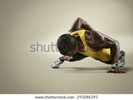 Sport. Young athletic man doing push-ups. Muscular and strong guy exercising. Isolated