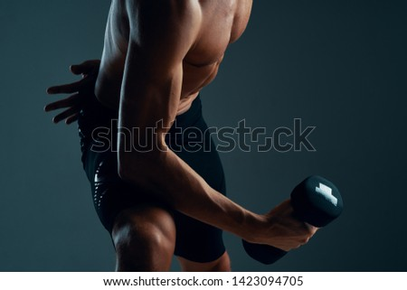 Sporting muscled muscular man with dumbbell in the hands of a fitness biceps workout