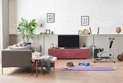 Sportive and training decoration interior room, nobody, television unit, grey sofa and blanket. Purple mat and blue dumbbell on the parquet, white brick wall background.