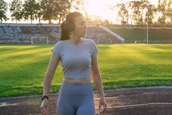 sportive beautiful girl in headphones at stadium. Fit woman at football field