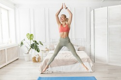 Sportive beautiful woman exercise at home, doing jumping jacks. Happy blonde-hair female fitness trainer is working out, smiling, healthy lifestyle and everyday training concept. High quality photo