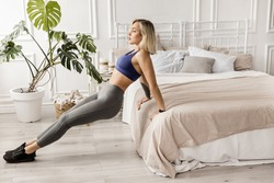 Sportive blonde girl in gray sportswear, bra and leggings goes in for sports, does back push-ups from the bed, plank pose, sportive girl works out at home or in a yoga studio.Healthy lifestyle concept