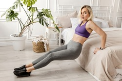 Sportive blonde girl in gray sportswear, goes in for sports, does back push-ups from the bed, plank pose, sportive girl trains at home or in a yoga studio. The girl is worried about her figure.