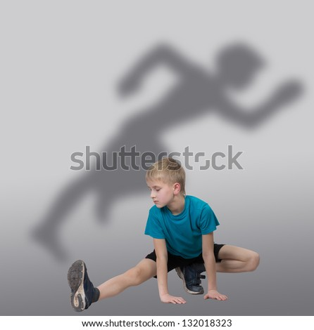 Sportive boy stretching his leg with runner's silhouette behind him