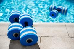Sportive equipment for aqua aerobics. Plastic dumbbells for aqua fitness at swimming pool on summer day outdoors, nobody