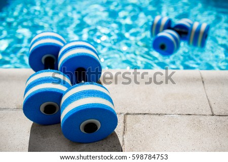 Sportive equipment for aqua aerobics. Plastic dumbbells for aqua fitness at swimming pool on summer day outdoors, nobody