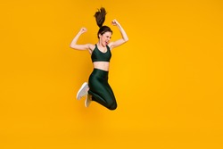 Sportive excited lady jump high active motivated person wear sports suit shoes isolated yellow color background