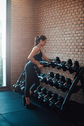 Sportive female person in black sportswear puts back dumbells to stand. Different dumbells and weights.