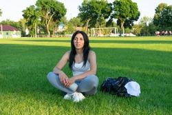 Sportive girl at stadium. Fit woman relaxing at football field. Shape beautiful girl