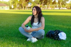 sportive girl with sportive equipment resting at the football field. fit girl