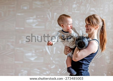 Sportive happy mother and son and kettlebell in hands. Motherhood is not a cause to let oneself go