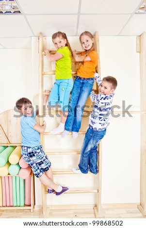 Sportive kids climbing on wall bars