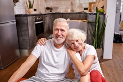 sportive man and woman 50-60 years old sit on the floor taking a break after workout, sport exercises, look at camera smiling, happy together