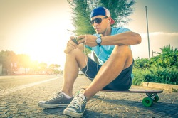 Sportive man at sunset listening music and looking at phone