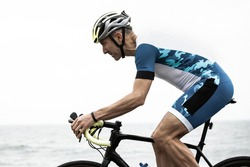 Sportive man riding bicycle near sea. Side view of sportsman in helmet and sportswear cycling near body of water during daytime. Triathlon concept