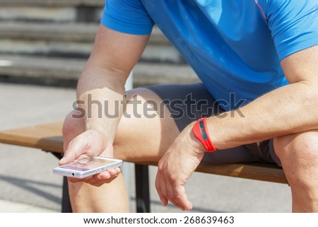 Sportive man sits on a bench and checks his fitness results on a smart phone. He wears a fitness tracker wristband on his left arm. #268639463