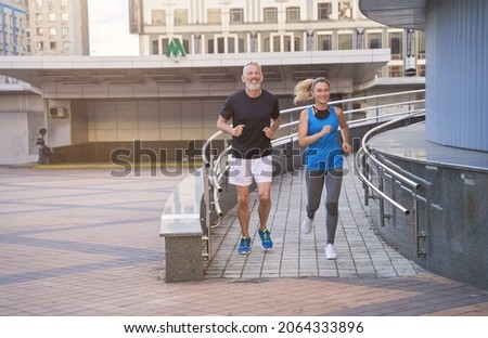 Sportive middle aged couple, man and woman in sportswear looking happy while running together outdoors, having cardio workout