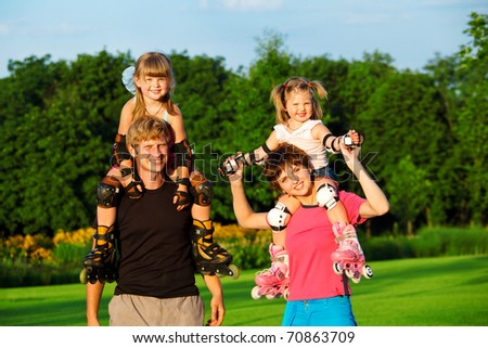 Sportive parents with kids in roller skates