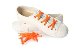 Sportive shoes with orange silicone laces on white background
