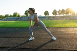 sportive woman at stadium doing stretching. fit girl at football field