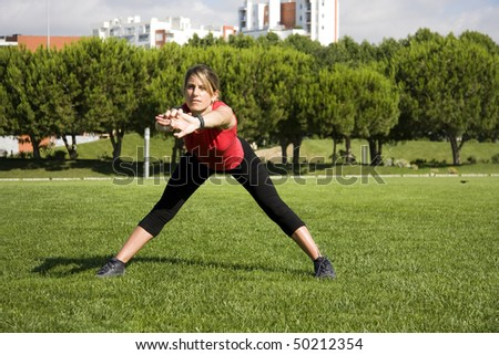 Sportive woman doing exercise on an urban park