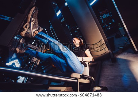 Sportive woman using weights press machine for legs at the gym. Pretty brunette exercising in a simulator. Girl in the gym exercises her legs #604871483